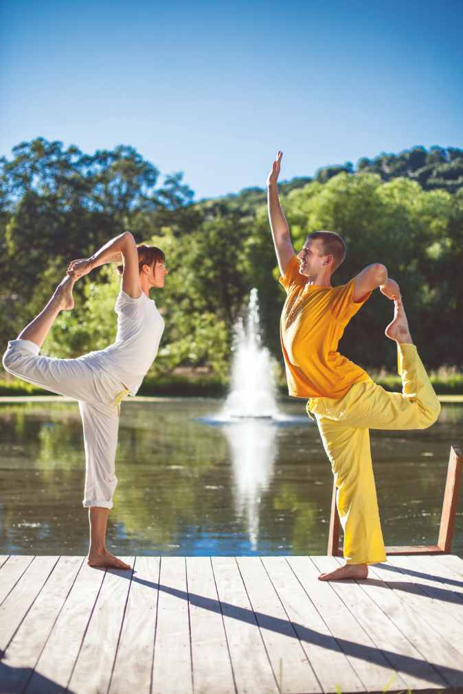 Two students practice the Yoga Pose called Nataraj.